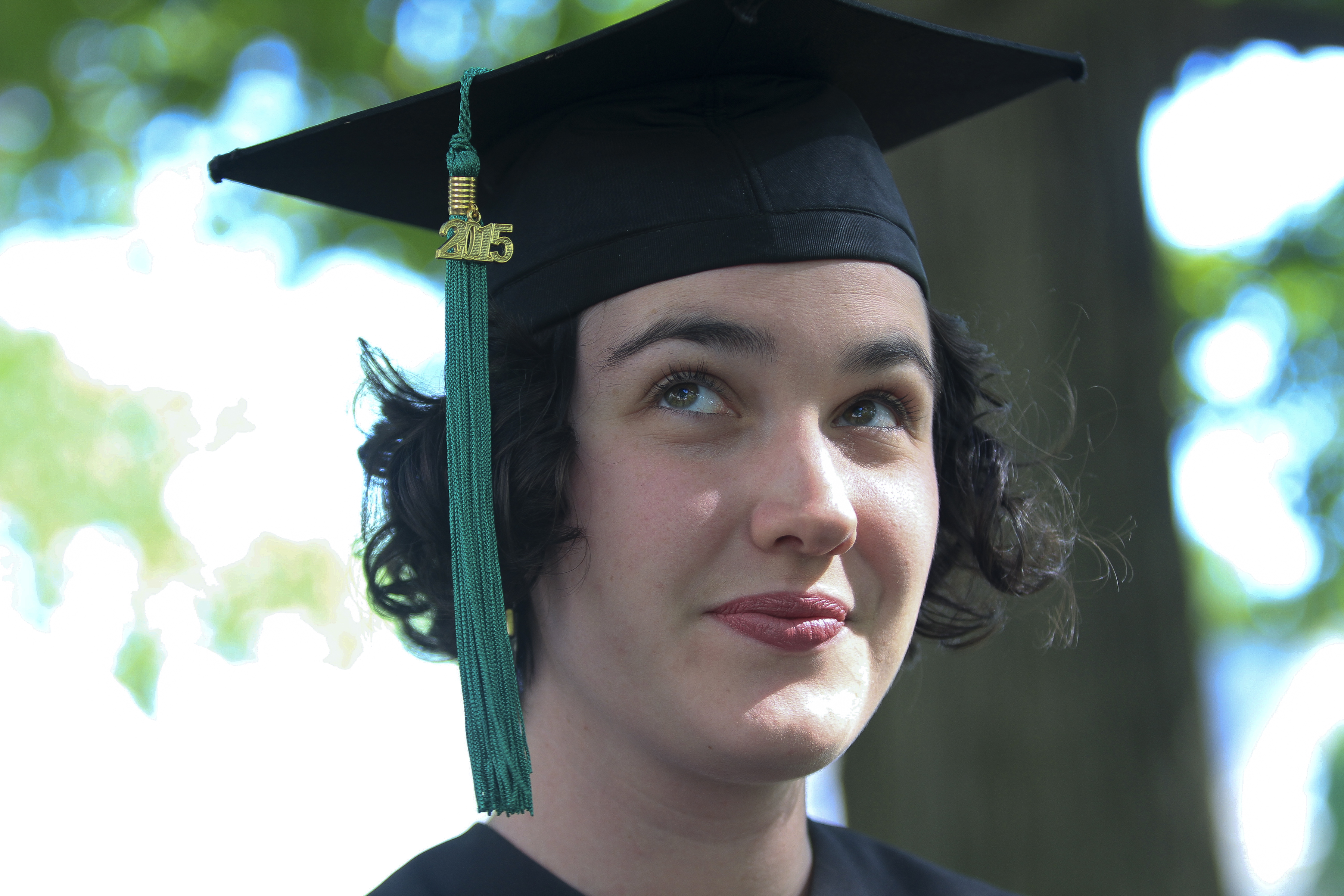 "The author in a graduation cap, with a green ""2015"" tassel, looking up into the left-hand edge of the photo."
